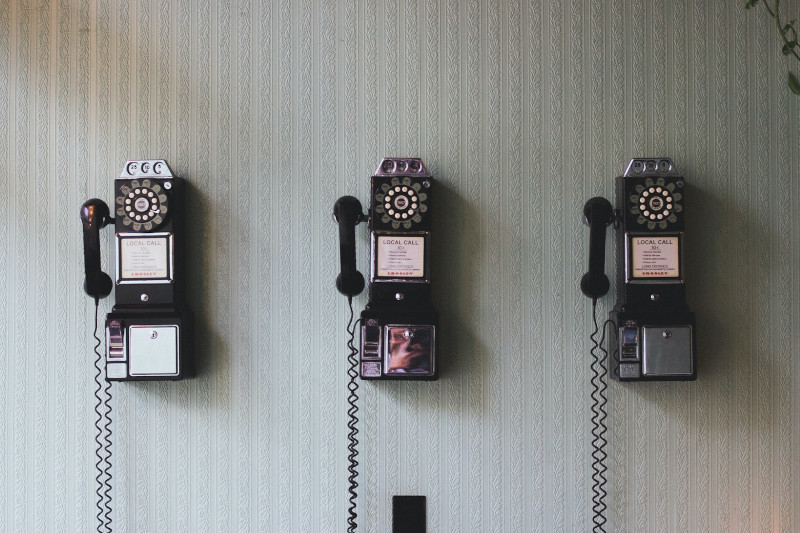 3 old style telephones hanging on an interior wall