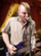 Martin Whiskin playing guitar on stage in Bristol
