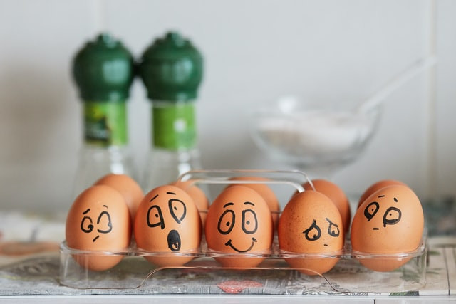 Eggs in an egg tray, with different facial expressions drawn on them