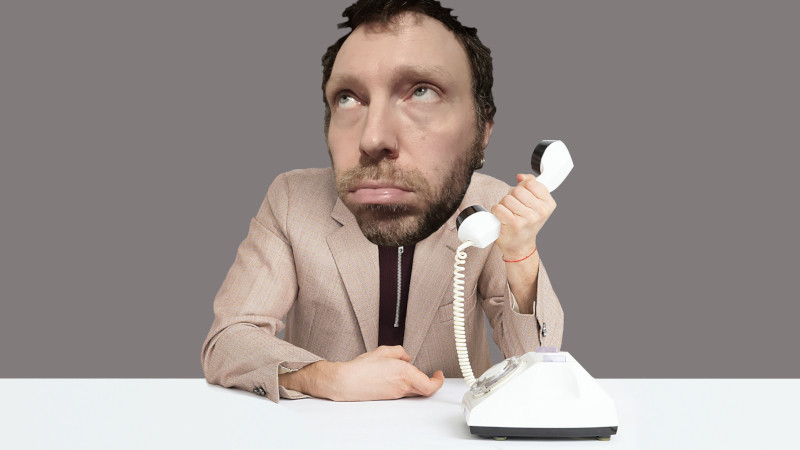 A grumpy looking man having to record his business telephone message