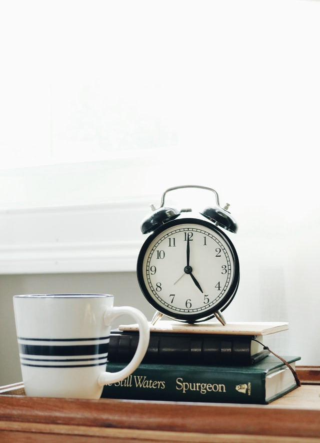 An alarm clock sits atop a pile of books with a coffee cup next to it