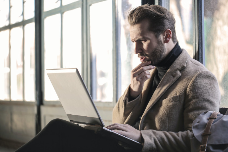 A smart gentleman with a laptop looking confused about what to buy online