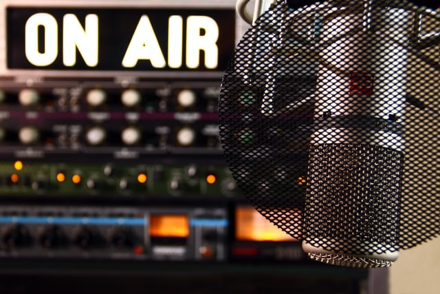 "A microphone hangs in front of an ""on air"" sign in a radio studio"