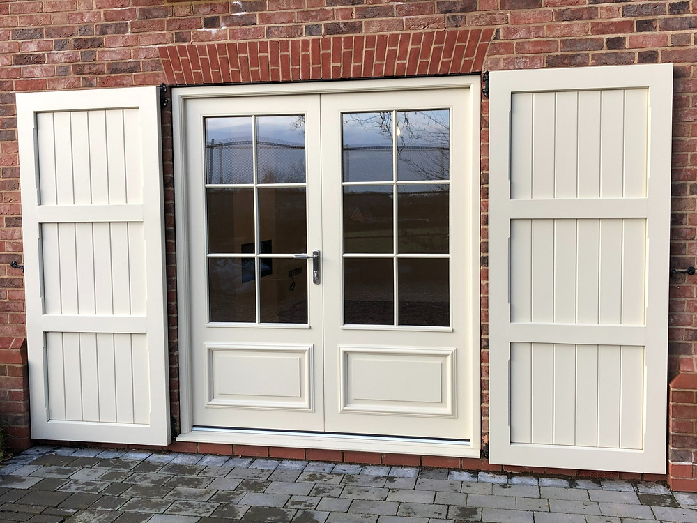 Painted Hardwood Shutters and French Doors with Raised and Fielded Panels and Bolection Mould.