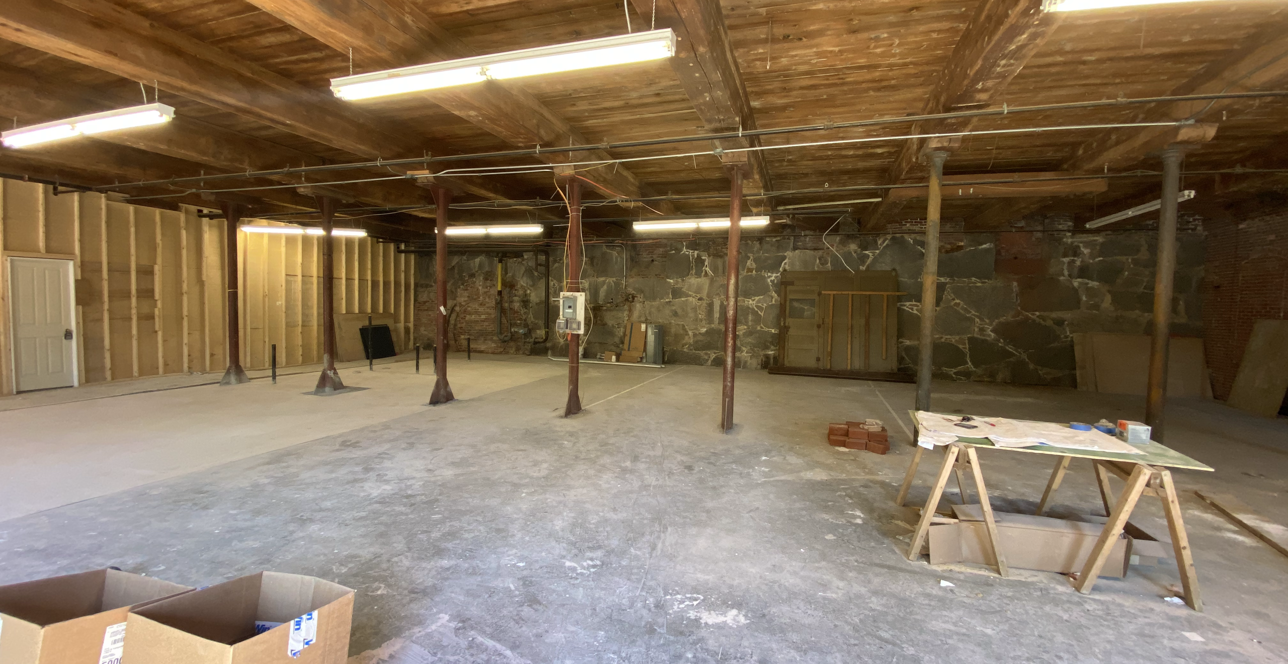Interior space fitted with existing concrete floors, ceiling beams, and stone