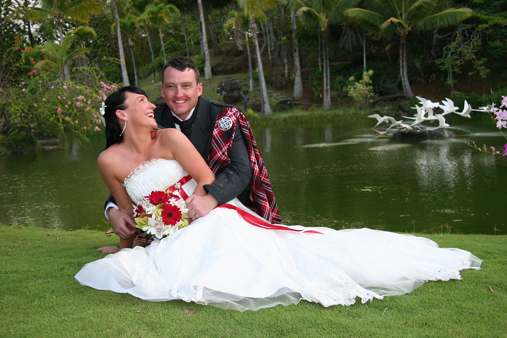 A bride and groom on the ground in front of a body of water.  The bride's looking at the groom behind her and smiling.