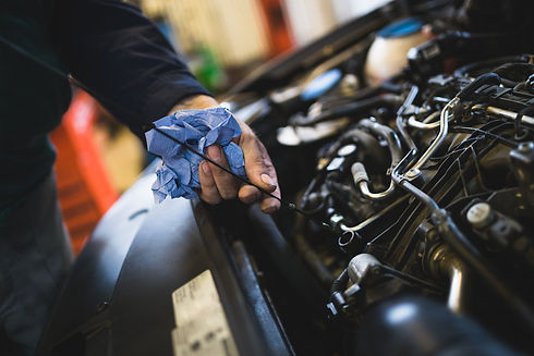 car mechanic checking the oil of a car