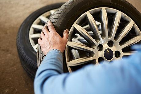 mechanic inspecting car tyre