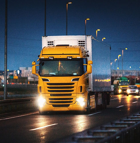 yellow lorry driving on the motorway at night