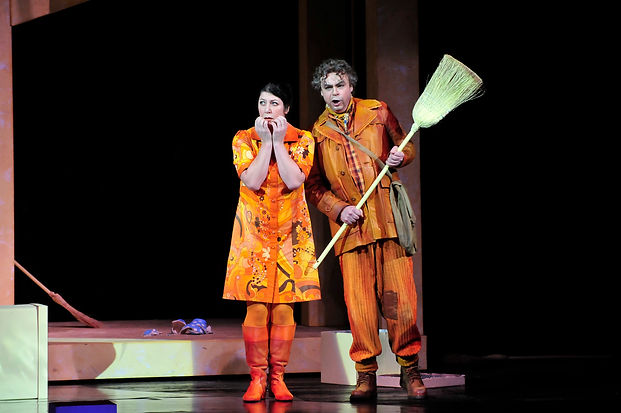 """Woman in orange dress and orange boots with her hands up towards her face is standing next to a man with a broom in his hand"""