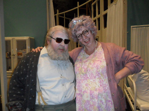 """Man with dark glasses, grey beard and a brown cardigan is standing next to a woman with a pink nightgown and a pink sweater wearing a tiara and smiling"""