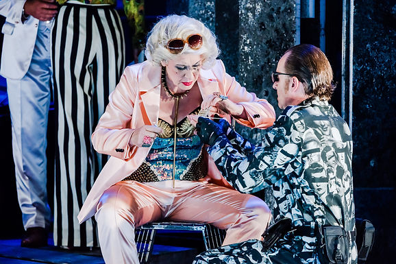 A woman in a pink suit is taking drugs in the opera Salome given by a man in an army suit. In the background striped trousers""
