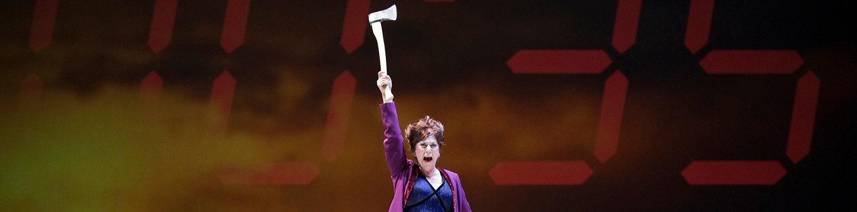 Elektra Ax Woman with purple dress standing in a sofa. Opera. Alarm clock on the wall.