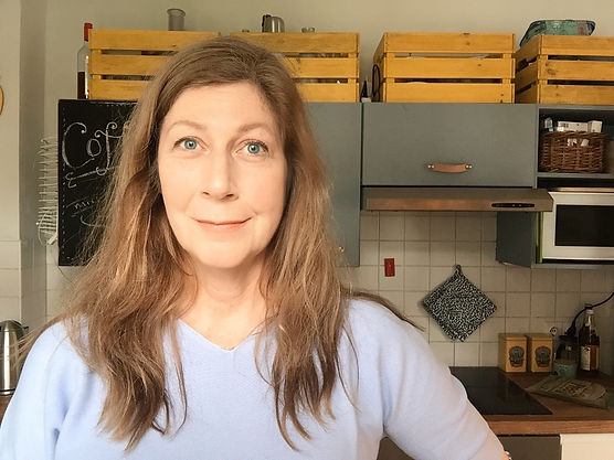 """Woman with lila sweater in a kitchen with oak worktop, grey cabinets and yellow crates"""""""