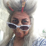 """""""Witch with gray hair and fake nose and a hen's fot on her head wears modern gray sunglasses"""""""