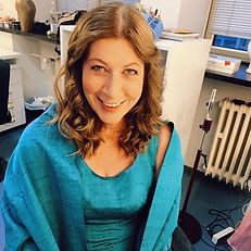 """""""Karin Lovelius in a turkoise galadress sitting in a chair in the makeup room at the opera with stage makeup and curly hair"""""""