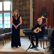 Karin Lovelius and Joakim Lundström in Stockholm Riddarhuset. In the background medieval plates and a big window with light streaming in. In focus singer and guitarist sitting beside""