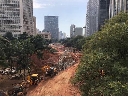 Fotos da reforma do Vale do Anhangabau. Há uma grande montanha de terra no centro da imagem, 3 tratores na esquerda e uma faixa de vegetação na direita da imagem. Ao fundo, é possível ver o prédio da prefeitura de São Paulo.