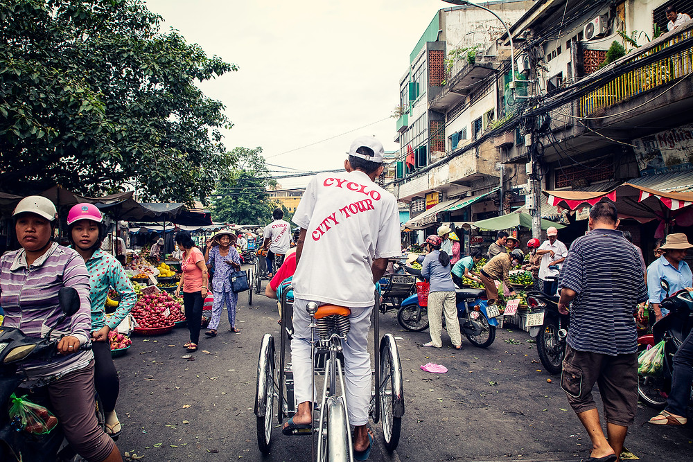 Mit der Rikscha fahren wir durch die schmalen Gasssen von Chinatown in Saigon