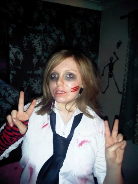 Me dressed as a zombie schoolgirl wearing a white shirt with tears and fake blood, a black tie and red and black stripey arm warmers. I have black makeup circles under my eyes and a special effects scratches on my cheeks.