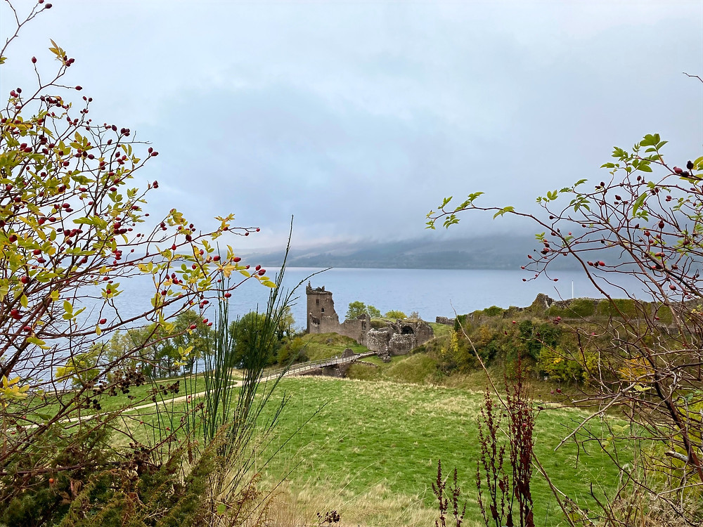 Ruins of a castle on the banks of a loch on a cloudy day.