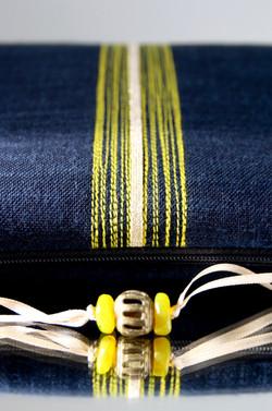 detail bande surpiquée fil jaune/ruban métal doré