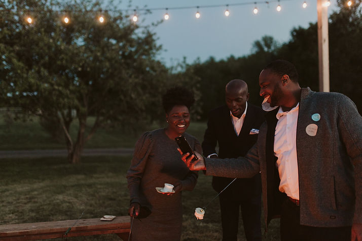 outdoor event space with 3 friends gathered around a fire and looking at a phone