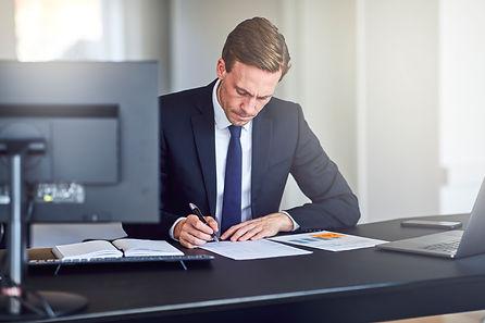 businessman-reading-through-paperwork-at