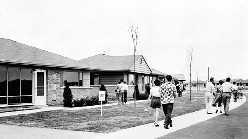 people walking down sidewalk park forest IL in the 1950s
