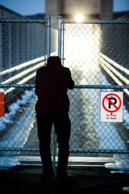 Man Looking Through a Fence