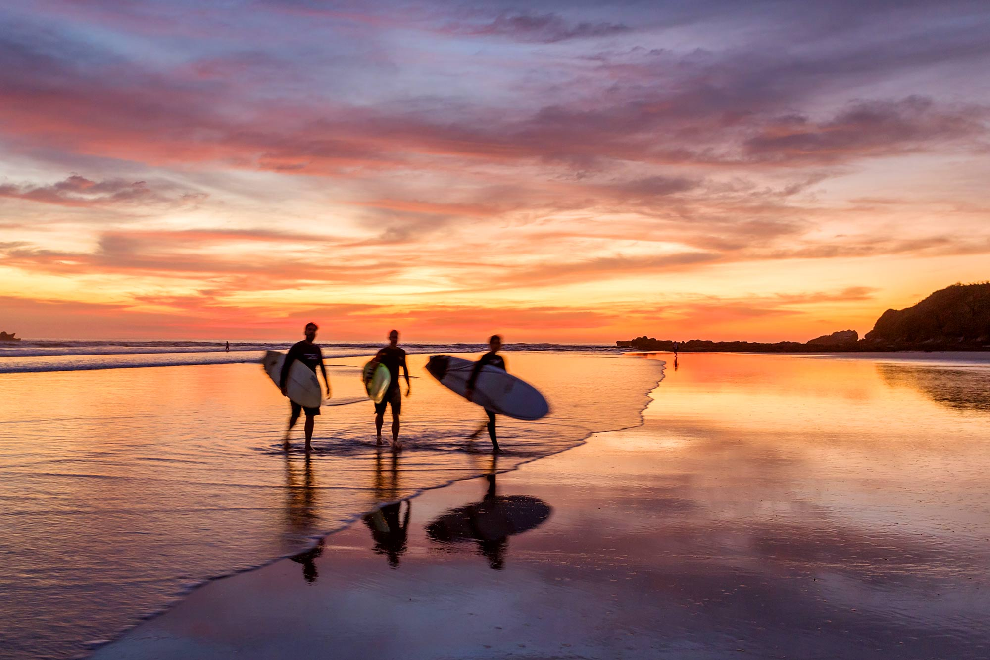 surfers-at-sunset-walking-on-beach--costa-rica-578363125-597a6810845b3400110e7da1