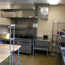 Commercial kitchen view of stove and work surface.