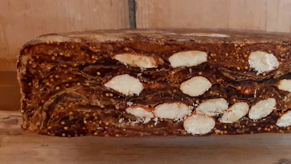 a slice of dried fig and almond cake on a wooden shelf