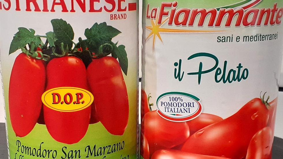 Colourful tins of italian tinned san marzano tomatoes on a slate board in front of white tiles