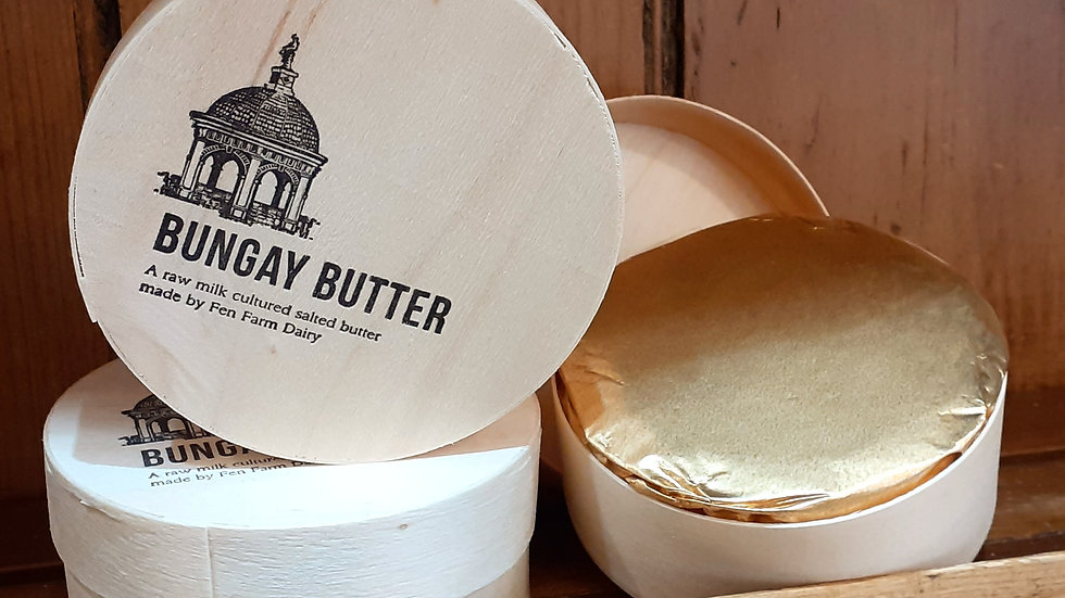 raw milk British cultured butter in wooden cheese boxes on wooden shelves