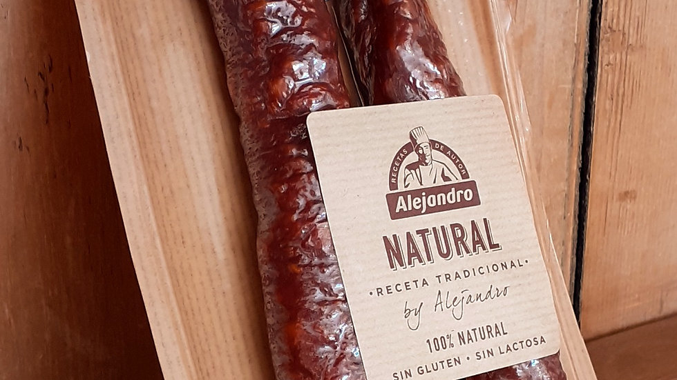 a spanish cured chorizo sausage in a packet with a brown label on a wooden shelf