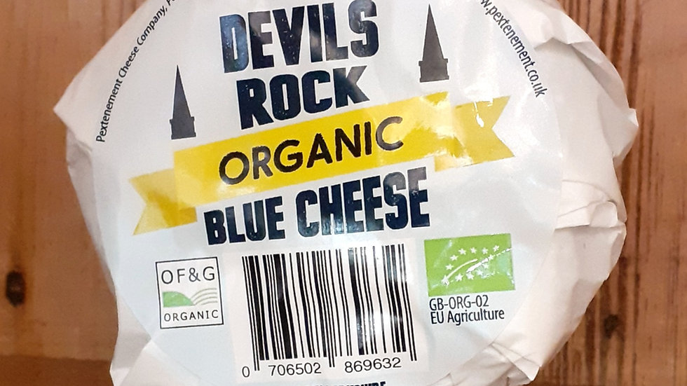 an organic blue cheese in its wrapper on a wooden shelf
