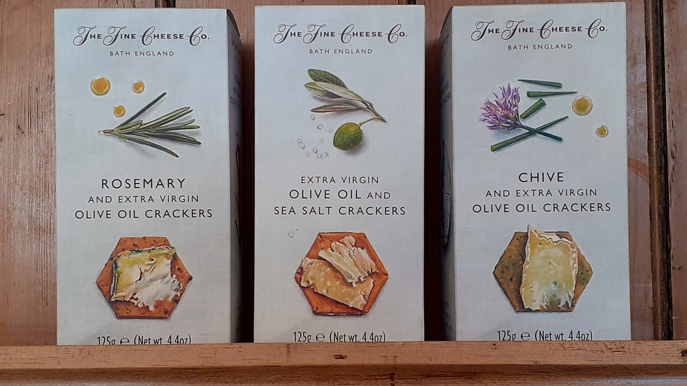 Cardboard boxes of crackers for cheese with illustrations of herbs on the packs on a wooden shelf