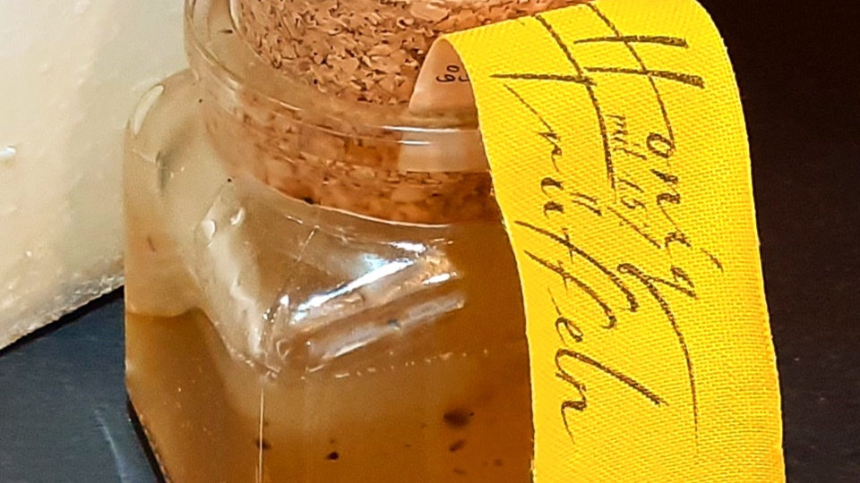 A glass jar of swiss truffle honey with a cork stopper and yellow label. black truffle honey