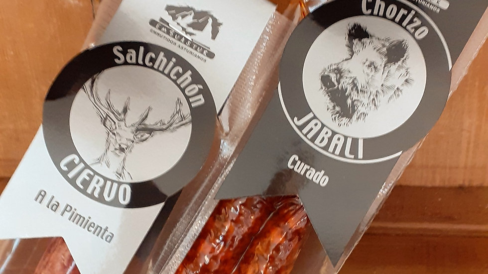 a game salami and a game chorizo in plastic vacpacs with card labels with spanish text on a wooden shelf