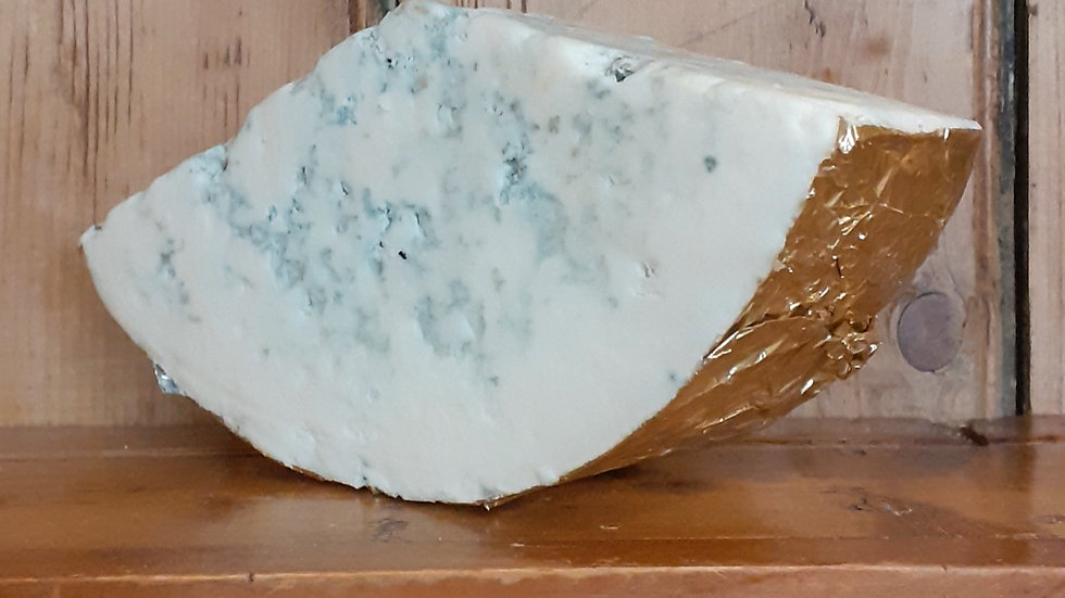 A piece of pale goat's milk blue cheese on a wooden shelf