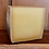 a large cut piece of aged mature alpine gruyere cheese with a brown rind on a wooden shelf