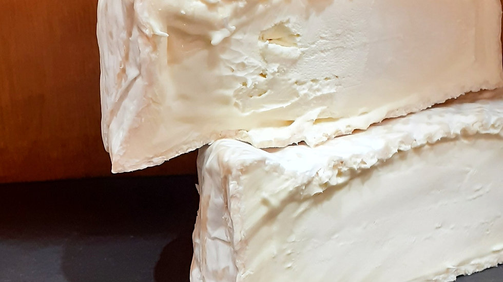 two slices of french triple cream full fat cheese white soft cheese on a slate on a wooden shelf