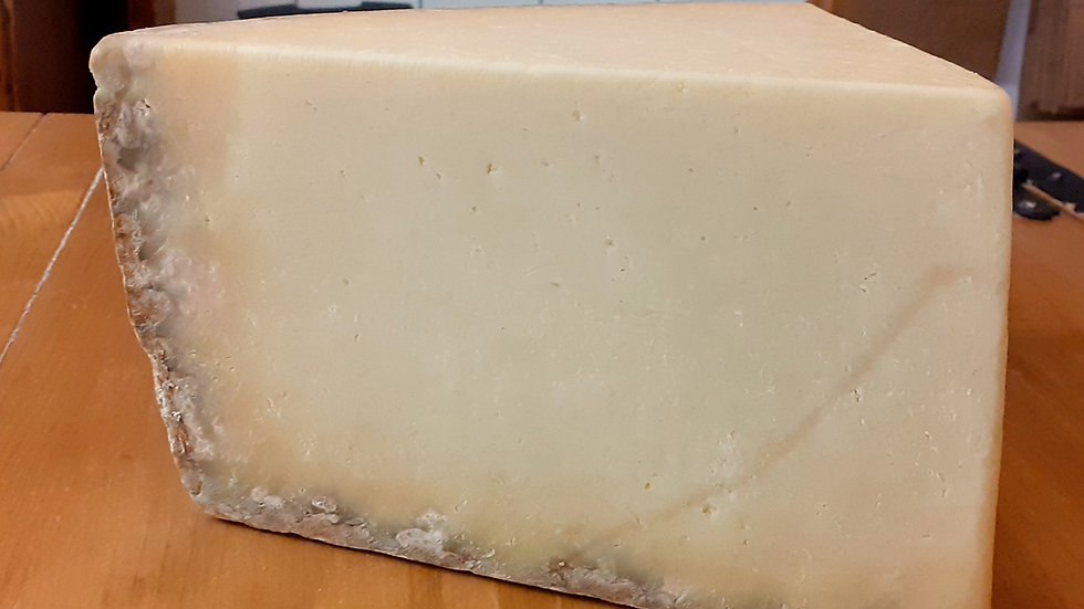a large cut piece of yellow french cantal salers cheese on a wooden surface