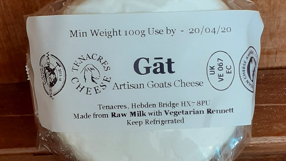 small white fresh goats cheese with monochrome label gat on wooden shelf