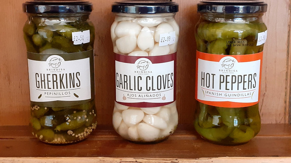 jars of spanish pickled garlic peppers chillis gherkins on a wooden shelf