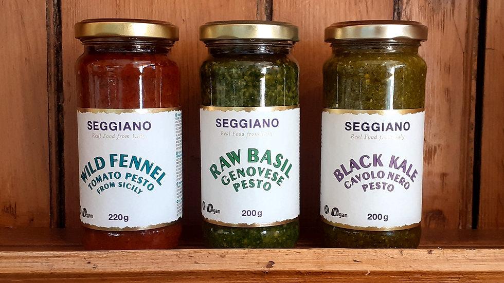 three jars of various italian made pesto on a wooden shelf