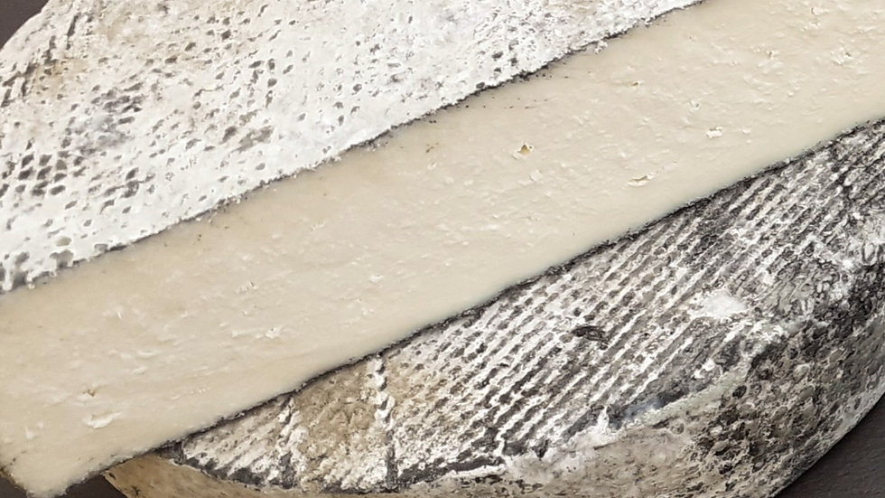an ash rind rinded hard goat's milk cheese with grey rind on a slate board