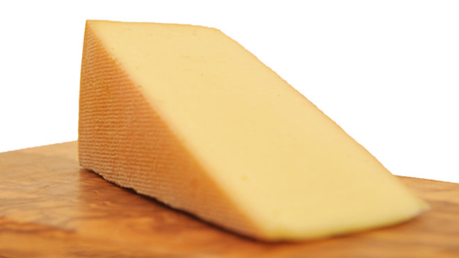 Slice of French Raclette Melting Cheese Brown Rind Yellow Cow's Milk Cheese