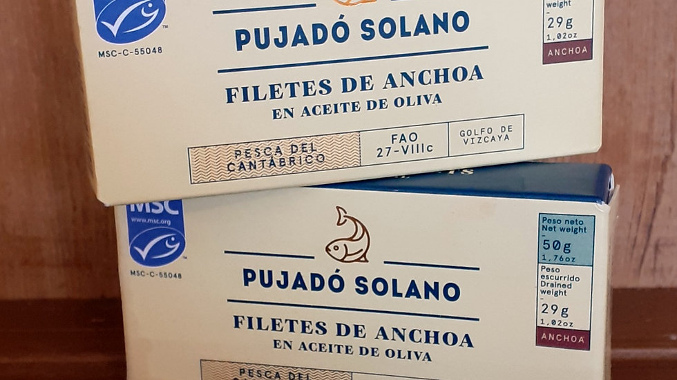 tins of salted anchovy fillets in cardboard boxes with spanish text on a wooden shelf